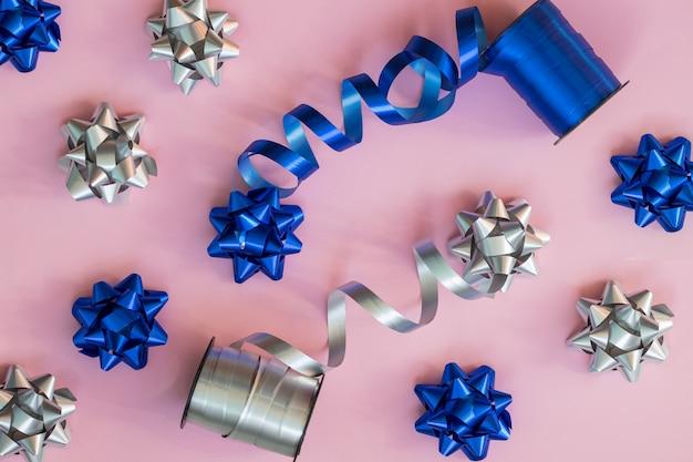 Tło wakacje. niebieskie i srebrne kokardy prezentowe. materiały do pakowania. przygotowanie świątecznych prezentów. skład mody na nowy rok lub ślub.