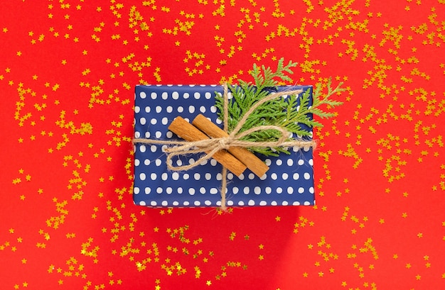 Tło wakacje, niebieskie pudełka na prezenty w kropki ze wstążką i kokardą oraz gałązki tui z cynamonem na czerwonym tle z brokatowymi złotymi gwiazdami, płaskie ułożenie, widok z góry