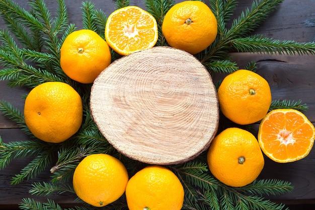 Tło wakacje noworoczne na okrągłym wycięciu drzewa otoczonego mandarynkami