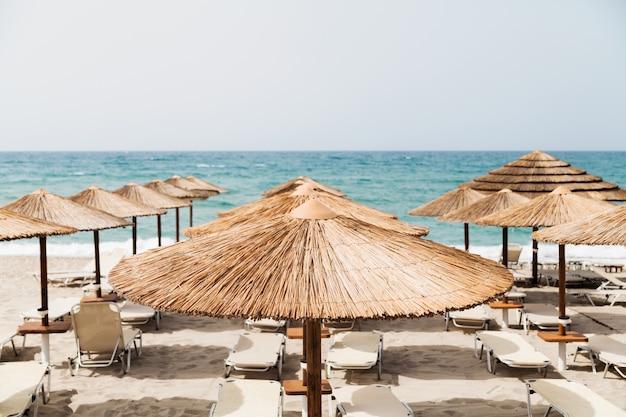 Tło wakacje. plaża z parasolami i widokiem na morze.