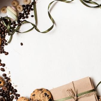 Tło wakacje prezentów i słodyczy. mały elegancki prezent na białym stole z domowymi ciasteczkami czekoladowymi i dekoracją ziaren kawy w pobliżu, zdjęcie z widokiem z góry z wolną przestrzenią