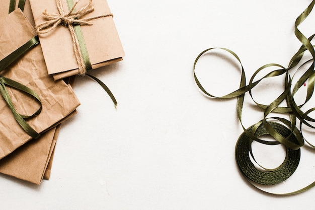 Tło wakacje prezentów. małe eleganckie ekologiczne prezenty zawinięte w papier rzemieślniczy na białym stole z ozdobnymi wstążkami, zdjęcie z widokiem z góry z wolną przestrzenią
