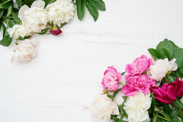 Tło wakacje. różowe i białe peonie rama na białym drewnianym tle. skopiuj miejsce, widok z góry.
