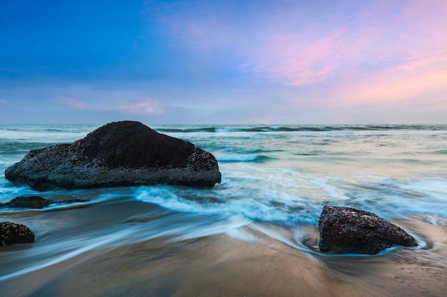 Tło wakacje tropikalnej plaży - fale i skały na plaży o zachodzie słońca