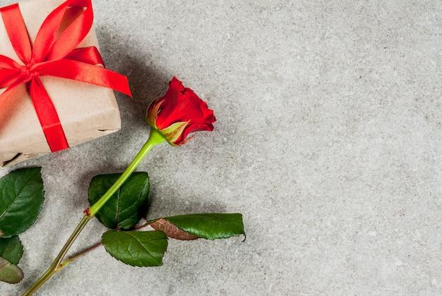 Tło wakacje, walentynki. bukiet czerwonych róż, krawat z czerwoną wstążką, zapakowane pudełko i czerwona świeca. na szarym kamiennym stole skopiuj widok z góry miejsca
