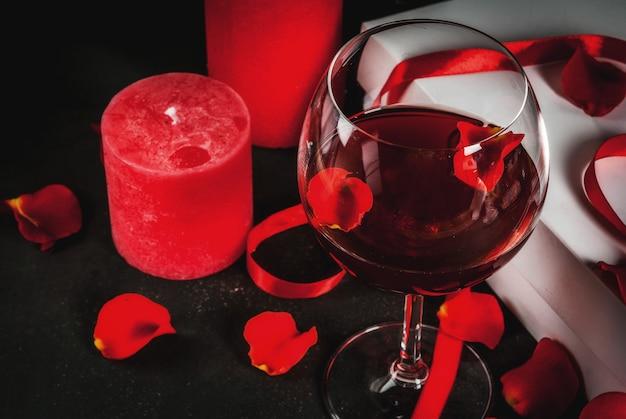 Tło wakacje, walentynki. bukiet czerwonych róż, krawat z czerwoną wstążką, zapakowane pudełko i czerwona świeca