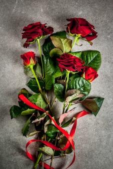 Tło wakacje, walentynki. bukiet czerwonych róż, krawat z czerwoną wstążką