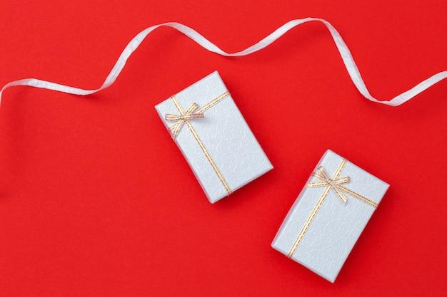 Tło wakacje z prezentami. dwa srebrne prezenty na czerwonym papierze