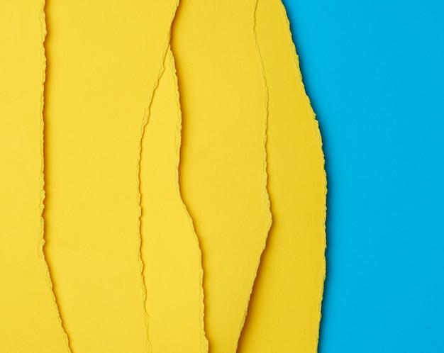 Tło warstwowy żółty rozdarty papier z cieniem na niebieskim tle