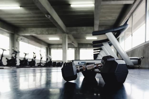 Tło widok z tyłu i białe hantle sprzęt na podłodze w centrum sportowym siłowni