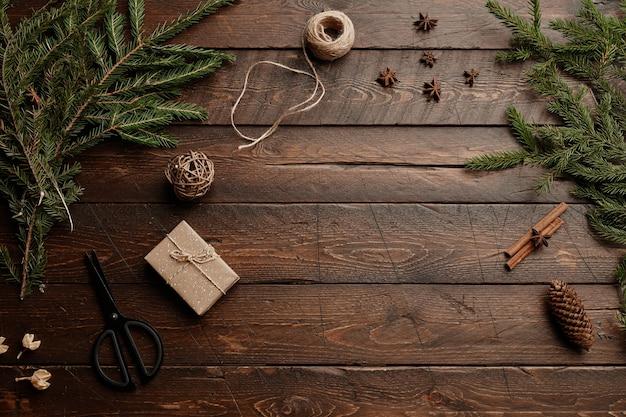 Tło widoku z góry z drewnianym stołem i rustykalnym opakowaniem prezentów świątecznych ozdobionym jodłą branc...