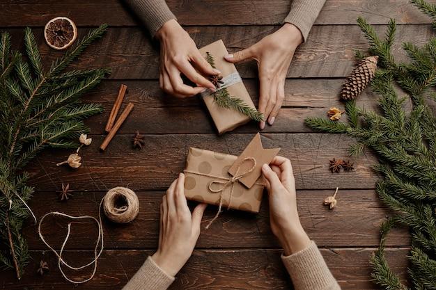 Tło widoku z góry z dwiema nierozpoznawalnymi młodymi kobietami pakującymi prezenty świąteczne przy drewnianym stole ...