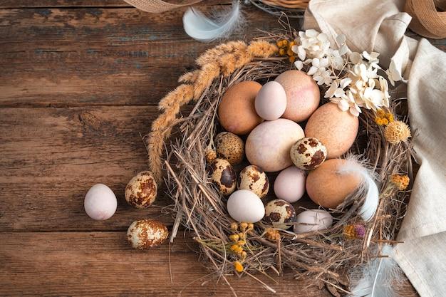 Tło wielkanoc. jaja przepiórcze i kurze jaja leżą w wiklinowym gnieździe ozdobionym kwiatami