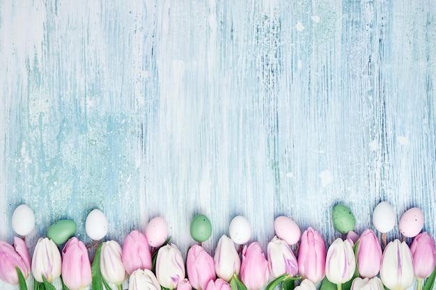 Tło wielkanoc. ozdobne pisanki i różowe tulipany graniczą na drewnianym tle.