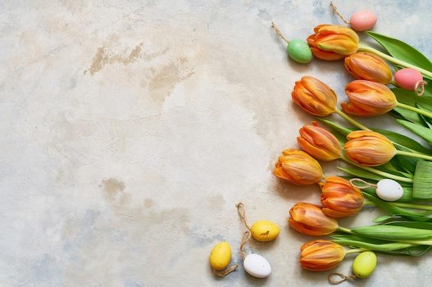 Tło wielkanoc. ozdobne pisanki i wiosenne tulipany na kolorowym tle. skopiuj miejsce, u góry