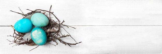 Tło wielkanoc z gniazda pisanki i gałązki na malowanym tle drewnianych. transparent. wesołych świąt wielkanocnych. gratulacyjne tło wielkanoc