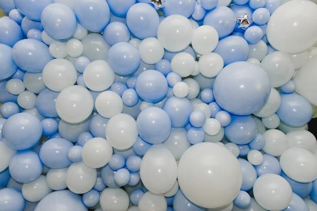 Tło wielu białych i niebieskich balonów. niebieskie i białe balony na przyjęciu urodzinowym