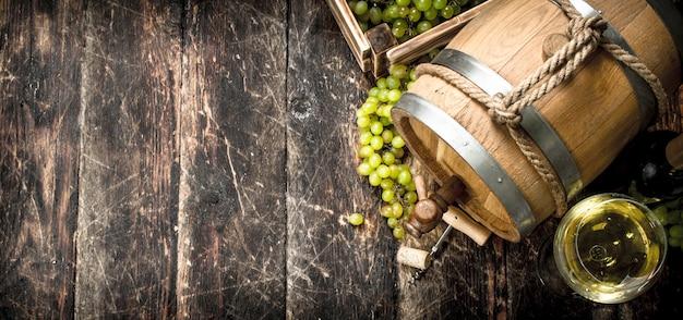 Tło wina beczka białego wina z gałęzi zielonych winogron na tle drewnianych
