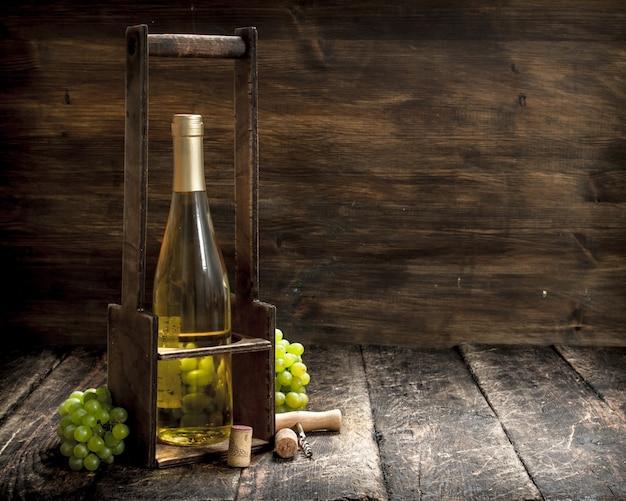 Tło wina białe wino na stojaku z gałęzi świeżych winogron na tle drewnianych