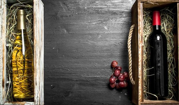 Tło wina. butelki na wino czerwone i białe w pudełkach. na czarnej tablicy.