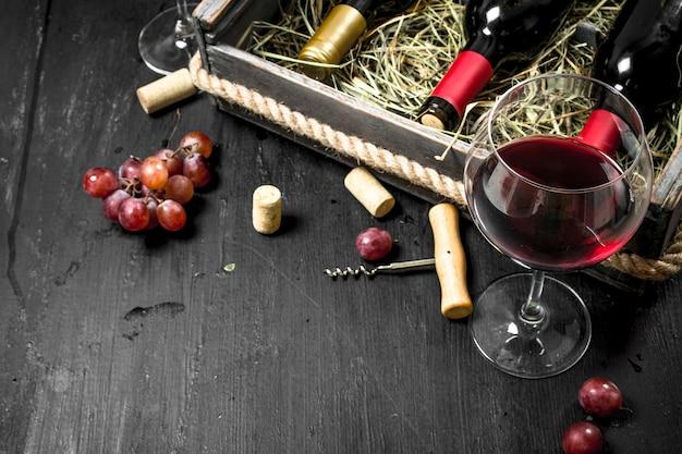 Tło wina. czerwone wino w starym pudełku z korkociągiem. na czarnej tablicy.