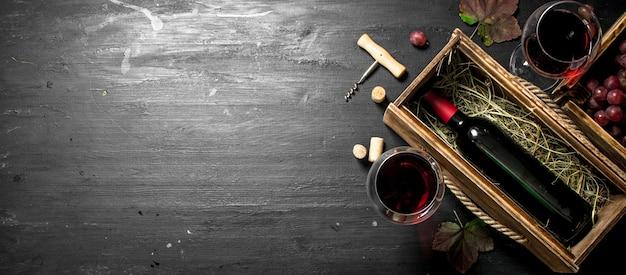 Tło wina. czerwone wino w starym pudełku z korkociągiem.