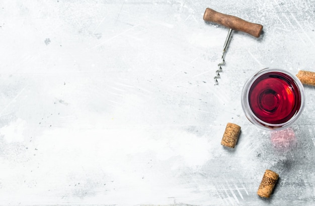 Tło wina. kieliszek czerwonego wina i korkociąg. na rustykalnym stole.