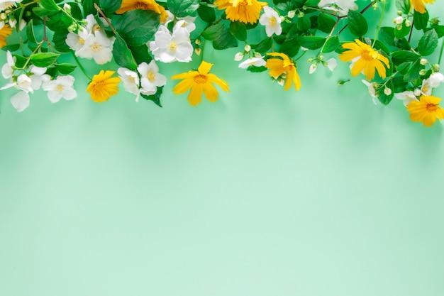 Tło wiosna. naturalne świeże kwiaty na tle mięty, widok z góry.