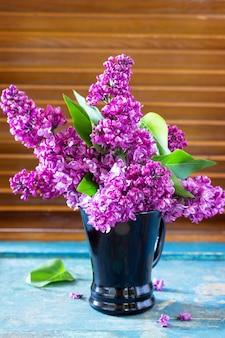 Tło wiosna. piękny świeży bukiet bzu z fioletowymi kwiatami w kieliszku.