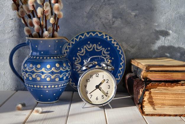 Tło wiosna z budzikiem, ceramicznym talerzem i dzbanem z wierzbą cipki i starymi książkami o drewnie