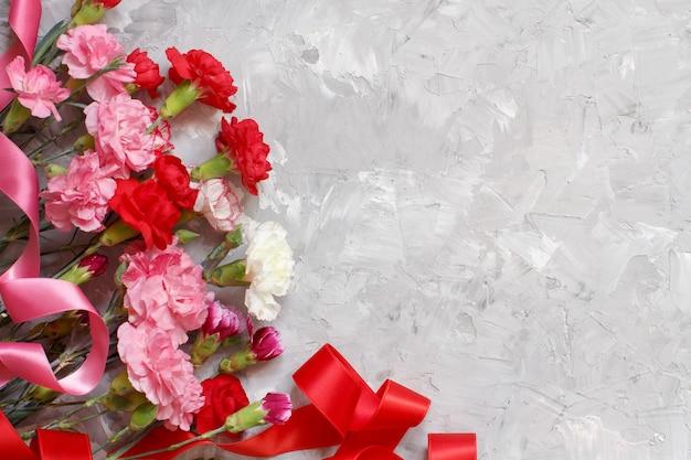Tło wiosna z kwiatów goździków i wstążkami