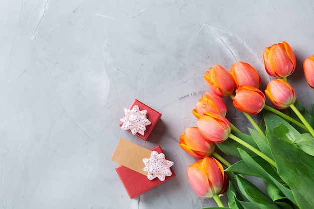 Tło wiosna z pomarańczowymi kolorowymi tulipanami i pudełkiem na prezenty, kobiety, dzień matki, kartka z życzeniami, płaski obraz przestrzeni świeckiej i kopiowania