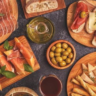 Tło włoskie jedzenie z szynką, serem, oliwkami, chlebem i winem