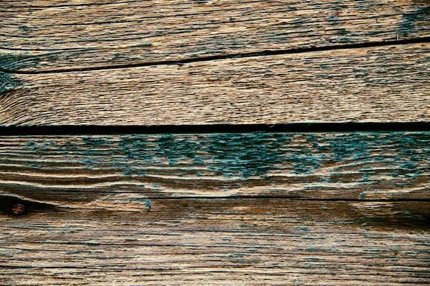 Tło wykonane ze starych desek pokrytych łuszczącą się farbą. faktura surowego i szorstkiego drewna.