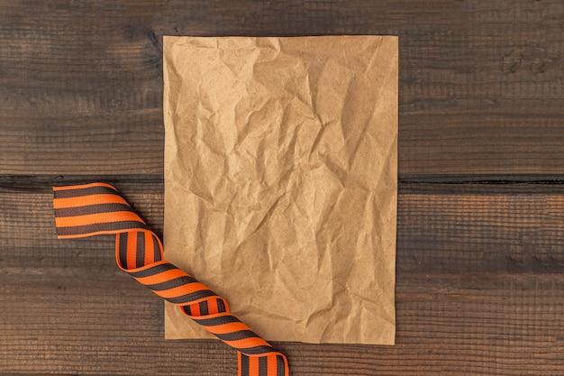 Tło z 9 maja - wstążka george i papier firmowy na drewnianym tle. koncepcja dzień zwycięstwa lub dzień obrońcy ojczyzny. widok z góry, kopiowanie miejsca na tekst