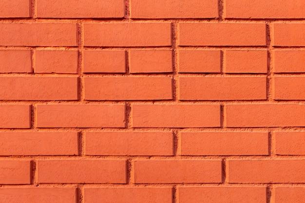 Tło z cegły, nierówna tekstura ściana pomalowana na kolor czerwony