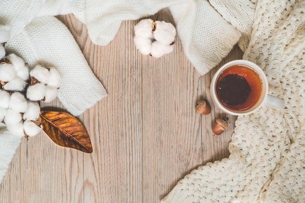 Tło z ciepłymi swetrami i filiżanką herbaty. przytulna martwa natura w ciepłych odcieniach. koncepcja jesień zima.