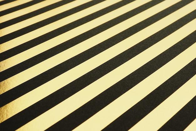 Tło z czarnymi i złotymi ukośnymi paskami folii.