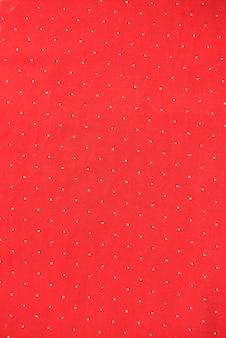 Tło z czerwonego materiału z białym tłem w kropki