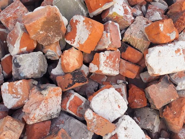Tło z czerwonej cegły. stos starych uszkodzonych starych połamanych zniszczonych bloków.