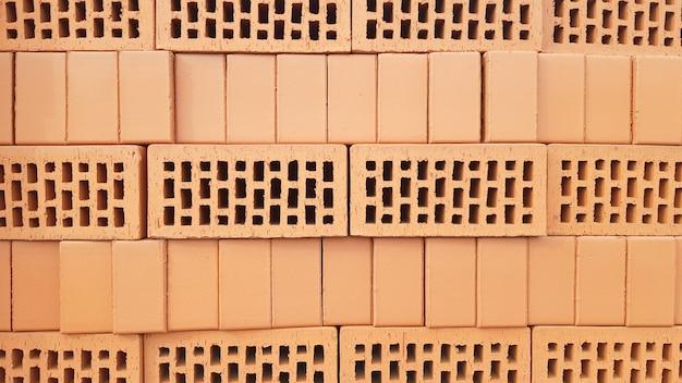 Tło z czerwonej cegły z otworami. czerwona cegła perforowana z prostokątnymi otworami. szorstki tekstura rzędów czerwonych cegieł światła. widok falistej strony i perforowanych górnych powierzchni cegły glinianej.