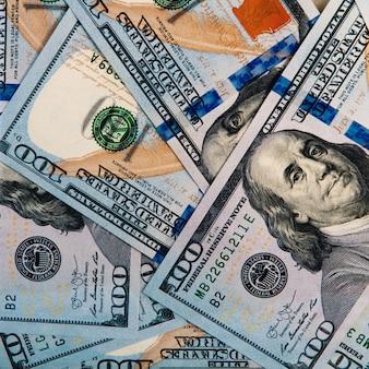 Tło z dolarów. w tle rozrzucone są banknoty o wartości stu dolarów amerykańskich.