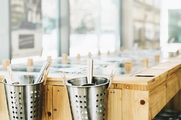 Tło z drewnianymi półkami z pojemnikami na żywność wielokrotnego użytku w plastikowym wolnym sklepie spożywczym