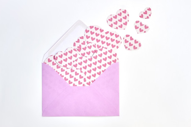 Tło z dużą ilością papierowych serc. różowa koperta z różowymi postaciami w kształcie serca wycięte z papieru na białym tle.