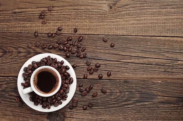 Tło z filiżanką kawy i ziaren kawy na starym drewnianym stole. widok z góry