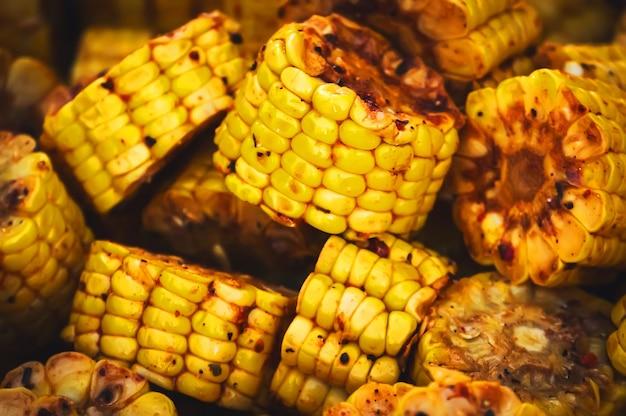 Tło z grillowanych warzyw na grilla. tło żywności z pieczonej kukurydzy. pojęcie zdrowej naturalnej żywności. kuchnia tradycyjna. marynowane kawałki kukurydzy do grillowania.
