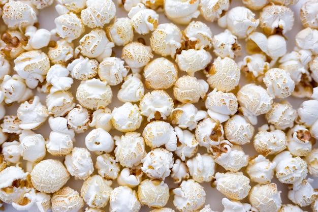 Tło z jedzeniem i rozrywką - zbliżenie chrupiącego solonego popcornu