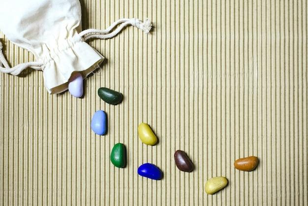 Tło z kolorowych fałszywych kamieni rozrzuconych na falistym papierze z saszetki z tkaniny.
