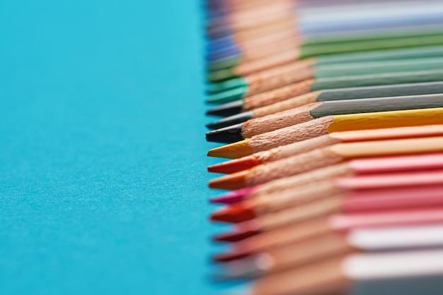 Tło z kolorowych ołówków na niebieskim papierze