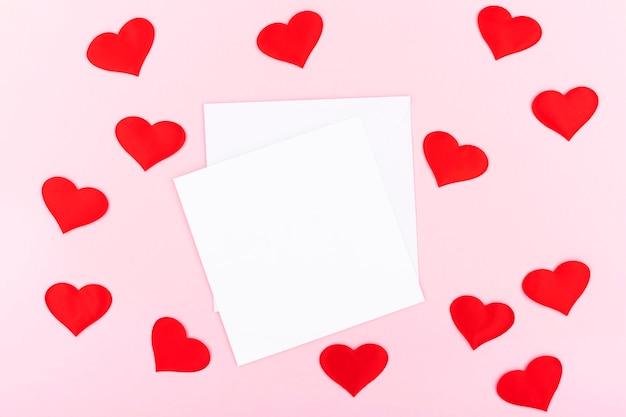 Tło z koperty, serca z wolnym miejscem na tekst na pastelowym różowym tle. widok płaski, widok z góry. koncepcja walentynki. koncepcja dnia matki.
